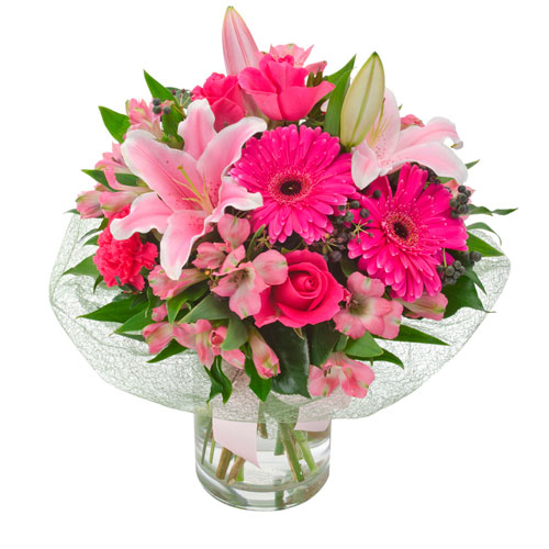 Pink lilies, roses in a clear glass vase